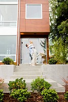 Man hugging and lifting woman on front stoop of modern house