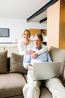 Portrait of woman hugging man using laptop in living room