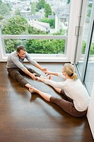 Couple stretching with feet and hands touching (thumbnail)