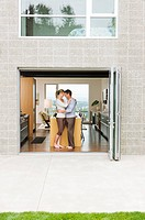 Hugging couple standing in open patio doorway