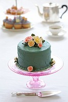 Sponge cake covered in blue cream & decorated with sugar roses