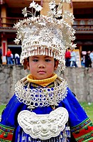 a child of the Miao minority is wearing a handmade silver headdress during a festival, China. Miao minority like use silver make clothes,they like sil...