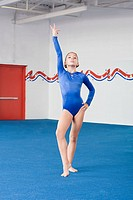 A gymnast with her arm raised