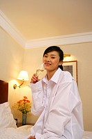 Young Woman Tasting Champagne On Hotel Bed