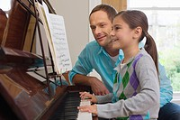 Father teaching daughter how to play the piano
