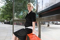 Female office worker at bus stop