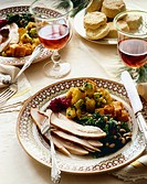 Holiday Dinner Plate with Turkey and Sides on Dinner Table with Wine and Biscuits