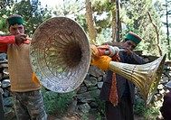 Two local men blowing large traditional wind instruments, Kalpa village, Recong Peo area, Kinnaur, Himachal Pradesh, India, Asia