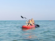 Mother and daughter paddle kayak in ocean shallows looking towards camera Egypt Red Sea Riviera Marsa Alam