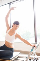 Woman working out on pilates equipment (thumbnail)