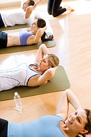 People on exercise mats doing sit_ups
