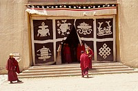 Lamas at monastery entrance, which is covered with a curtain depicting the sacred symbols of Buddhism, at Longki, south of Yushu in Qinghai, China, As...