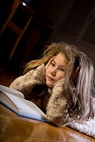 Concentrated little girl reading a book