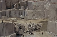 Men walking past clean faces for block extraction in granite quarry, Budduro, Sardinia, Italy, Europe