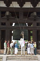 Tourists look at big cast iron bell, Todaiji Big Buddha Temple, constructed in the 8th century Nara City, Nara Prefecture, Honshu Island, Japan, Asia