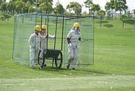 Women in a cage walk over the driving range to collect golf balls, Tomson Golf Club, BMW Asian Open 2004, Shanghai, China