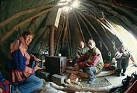 Sami man Lapplander inside laavo tent, drinking moonshine, Finnmark, Norway, Scandinavia, Europe