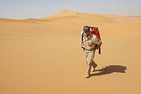 Ambulance officer with emergency bag is going in desert