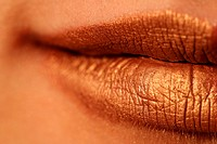 Macro blur image of bright lips _ gold lipstik