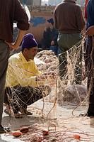 Fisherman repairing net, Essaouira harbour, Morocco, North Africa, Africa