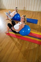 Two pregnant women practicing yoga together with exercise balls in exercise studio