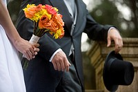 Close_up of midsection of bride and groom holding bouquet and hat