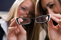 Close_up of two young women looking through eyeglasses