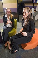 Two young multi_ethnic businesswomen sitting on chairs in office