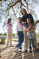 Portrait of young African American family outdoors in park, looking at camera