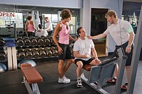 Mature couple in session with personal trainer at gym