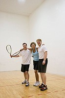 Portrait of mature couple with personal trainer at gym
