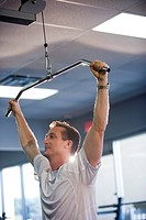 Portrait of mature man pulling weight machine at gym