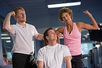 Portrait of mature couple with personal trainer in gym