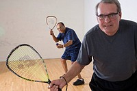 Multi_ethnic senior men playing racketball at indoor court, looking at camera