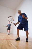 Multi_ethnic senior men playing racketball at indoor court