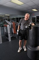 Portrait of senior man with boxing gloves at gym