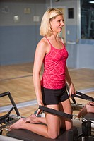 Young woman on Pilates exercise equipment in gym with mirror in background