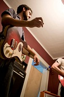 Young man playing guitar in house with band, low angle view