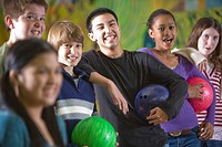 Happy multi_ethnic teenagers holding bowling balls, focus on background