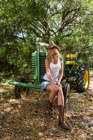 Young blonde cowgirl in cowboy hat sitting on tractor outdoors