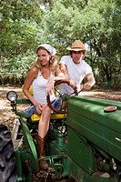 Young cowboy and cowgirl sitting on tractor outdoors