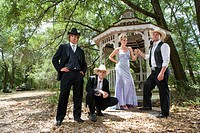 Young cowboys in western suits and young blonde woman in evening gown standing near gazebo outdoors
