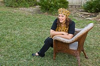 Portrait of happy African American mid adult woman dressed in traditional African attire sitting in yard outdoors