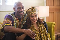 Portrait of happy African American couple dressed in traditional African attire sitting in living room indoors