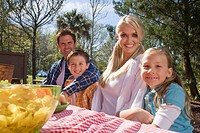 Portrait of young happy family sitting at picnic table near campsite