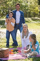 Young happy family in park with picnic basket