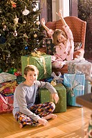 Portrait of brother and sister sitting next to Christmas tree and presents, looking at camera