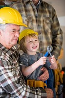 Close_up of grandfather and grandson wearing hard hats and holding tool