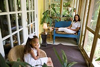 Portrait of happy African American mother and daughter relaxing together in sunroom