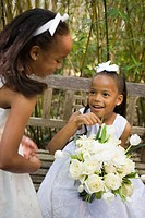 Happy African American flower girls outside on wedding day